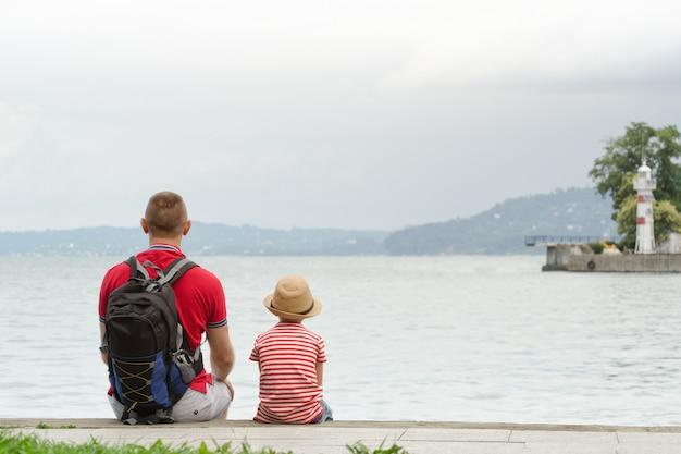 Padre e figlio seduti sul molo sullo sfondo del mare, faro e montagne in lontananza. vista posteriore