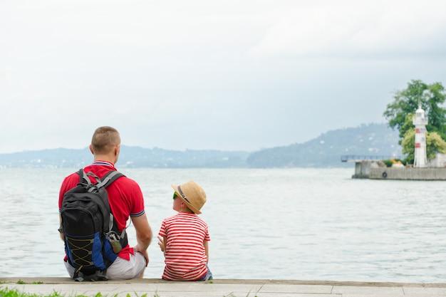 Padre e figlio seduti sul molo sullo sfondo del mare, faro e montagne in lontananza