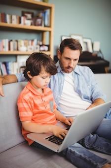 Padre e figlio seri che per mezzo del computer portatile mentre sedendosi sul sofà