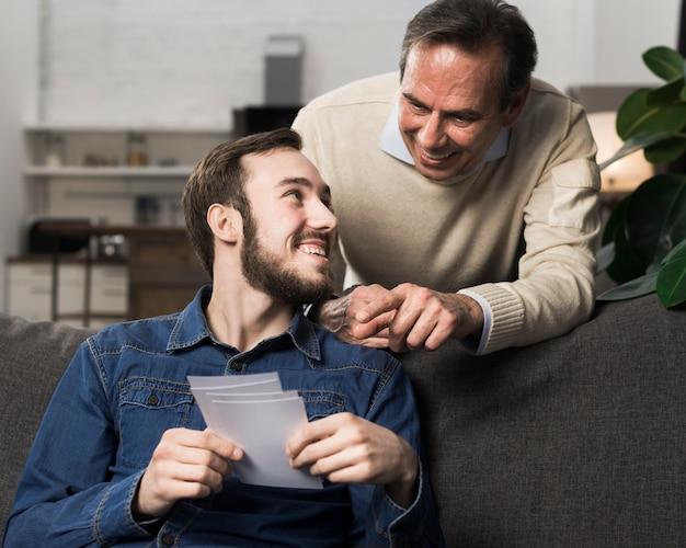 Padre e figlio si divertono e guardano le foto