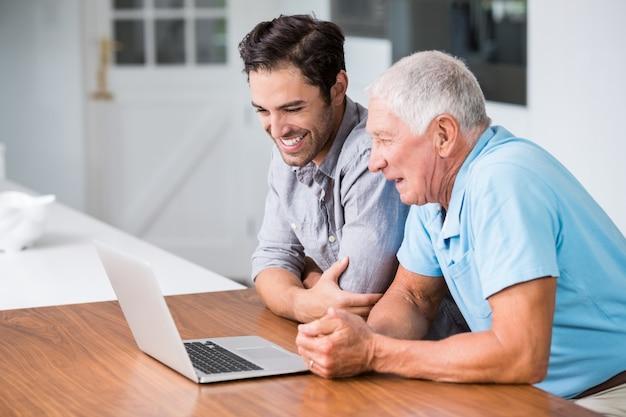 Padre e figlio sorridenti che per mezzo del computer portatile