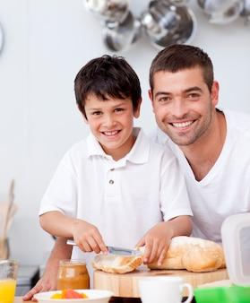 Padre e figlio sorridenti che preparano un pane tostato