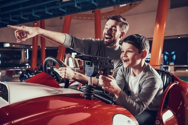 Padre e figlio sorridenti che si siedono insieme sulla festa dell'automobile del giocattolo