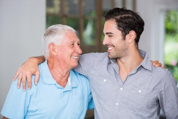 Padre e figlio sorridenti con il braccio intorno