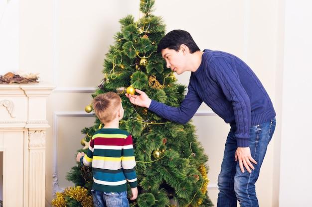 Padre e figlio stanno decorando l'albero di natale