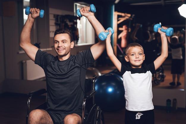 Padre e figlio stanno facendo esercizi con dumbbels