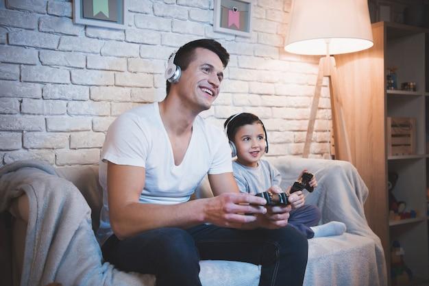 Padre e figlio stanno giocando a videogiochi in tv di notte.