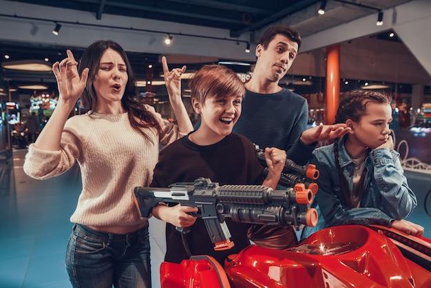 Padre e figlio stanno sparando pistole nere in arcade