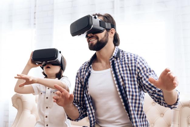 Padre e figlio, usando gli occhiali per realtà virtuale, giocano nel gioco.
