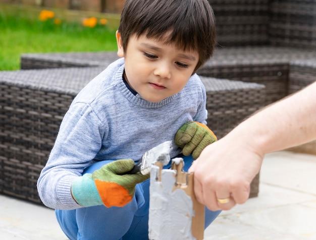 Padre e figlio usando il colore della pittura del pennello su cartone fuori nel giardino