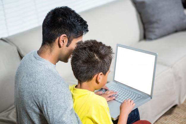 Padre e figlio usando il portatile sul divano
