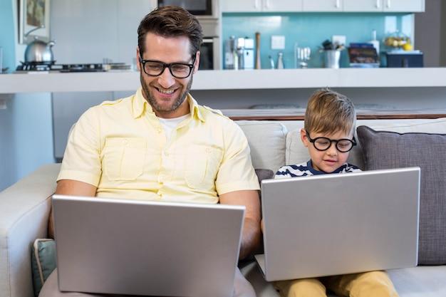 Padre e figlio utilizzando computer portatili sul divano a casa in salotto