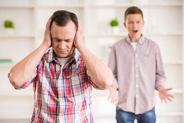 Padre e figlio vestiti casual avendo litigio a casa.