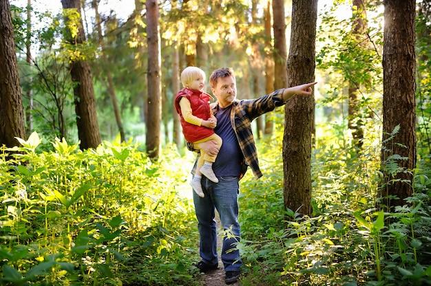 Padre e il suo piccolo figlio durante le attività di trekking nella foresta al tramonto