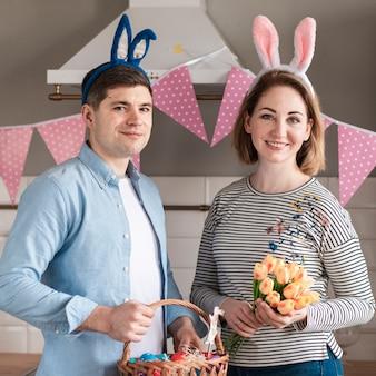 Padre e madre felici che posano con le orecchie del coniglietto