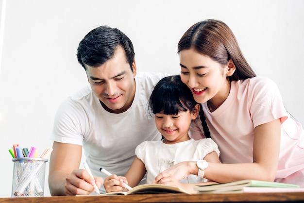 Padre e madre felici della famiglia con la figlia che impara e che scrive in taccuino con la matita che fa i compiti a casa concetto di istruzione