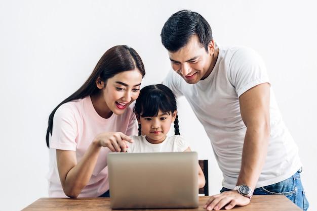 Padre e madre felici della famiglia con la figlia che si siede insieme e che esamina computer portatile nel salone a casa