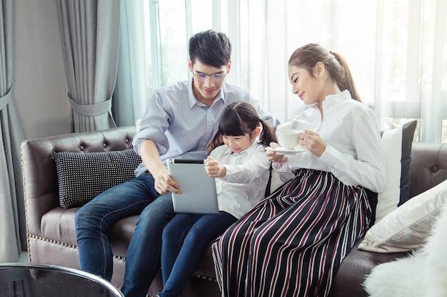 Padre e madre insegnando ai bambini a fare i compiti a casa, la famiglia asiatica è felice.