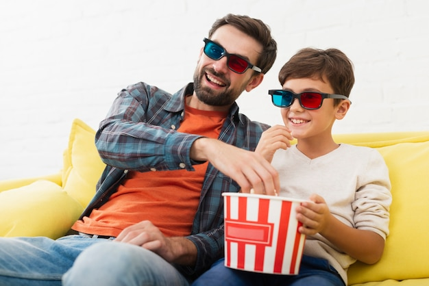 Padre e presto mangiando popcorn e guardando un film