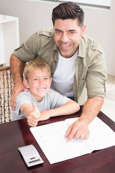 Padre felice aiutando il figlio con i suoi compiti di matematica a tavola