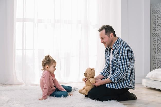 Padre felice che gioca con il suo bambino in casa