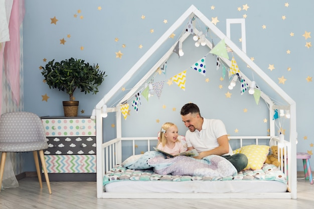 Padre felice che ride con la sua ragazza di 3 anni mentre era seduto sul letto della casa bianca nella camera da letto dei bambini