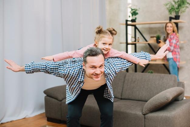Padre felice che trasporta sulle spalle piccola figlia con le braccia aperte
