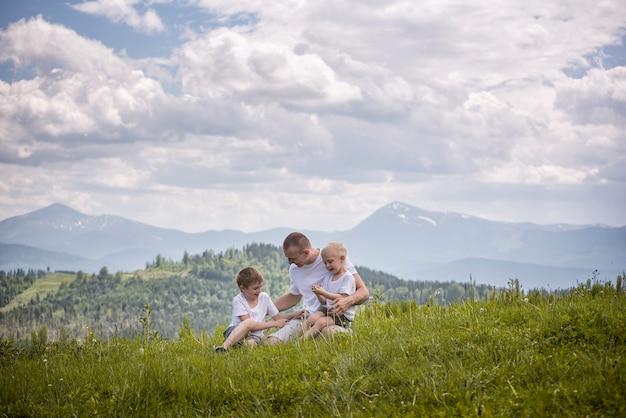 Padre felice con i suoi due giovani figli seduti sull'erba