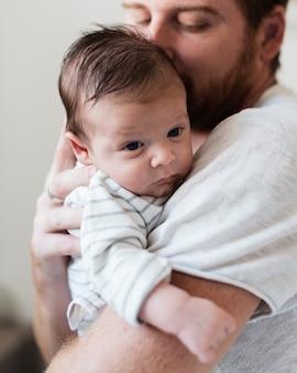 Padre felice del primo piano che bacia suo figlio
