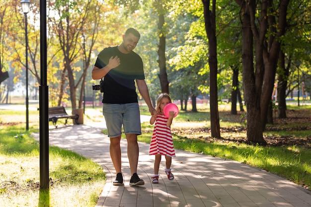 Padre felice e bambina che camminano tenendo in mano nel parco estivo
