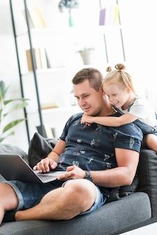 Padre felice e figlia che per mezzo del computer portatile a casa