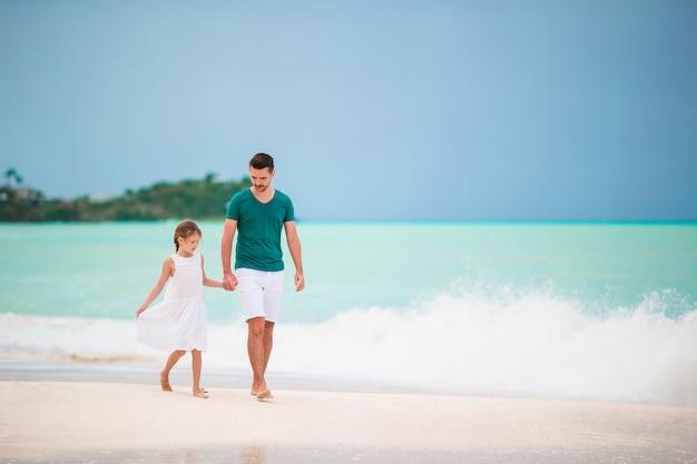 Padre felice e la sua adorabile figlioletta in spiaggia tropicale camminando insieme