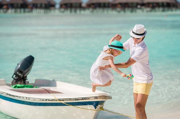Padre felice e la sua adorabile figlioletta in spiaggia tropicale divertendosi