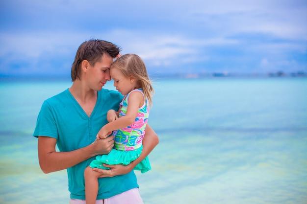 Padre felice e la sua adorabile piccola figlia in spiaggia di sabbia bianca