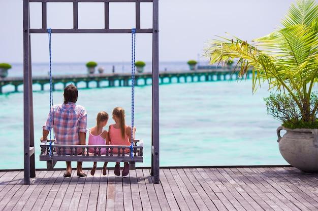 Padre felice e le sue adorabili figlie in spiaggia tropicale divertendosi