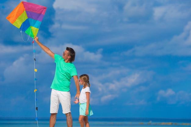 Padre felice e piccolo aquilone sveglio della figlia insieme alla spiaggia tropicale