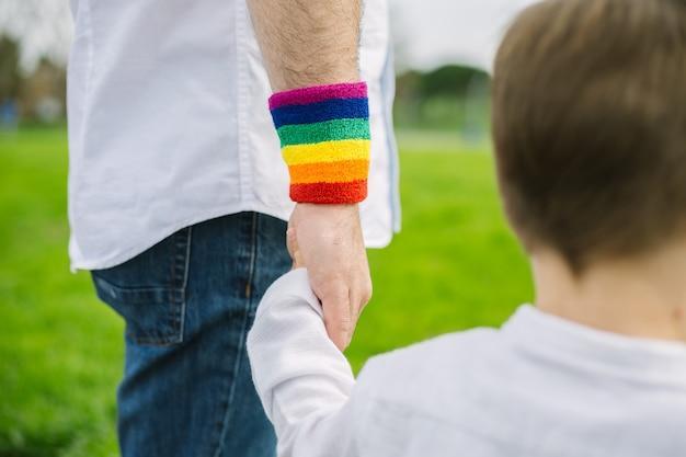 Padre gay e suo figlio adottivo che camminano nel parco. lgtb
