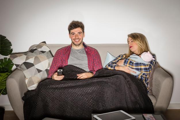 Padre guardando la tv mentre la madre con il bambino dorme
