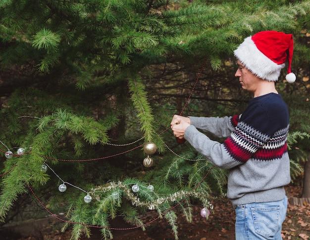 . padre in cappello rosso di natale che decora l'albero di natale all'aperto nel cortile della casa prima delle vacanze
