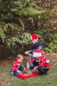 Padre in cappello rosso di natale e due figlie in maglioni rossi che decorano l'albero di natale all'aperto nel cortile della casa prima delle vacanze