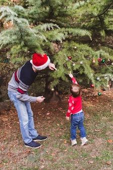 . padre in cappello rosso di natale e figlia in maglione rosso che decora l'albero di natale all'aperto nel cortile della casa prima delle vacanze