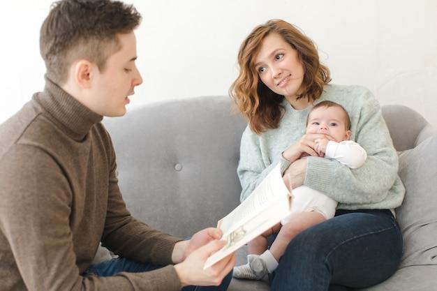 Padre leggendo il libro a figlio e madre