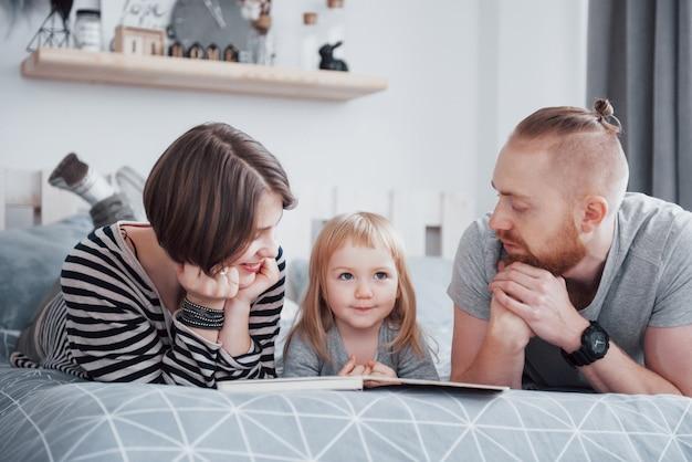Padre, madre e figlia piccola, leggendo il libro per bambini su un divano nel soggiorno. la grande famiglia felice ha letto un libro interessante in un giorno festivo. i genitori adorano i loro figli