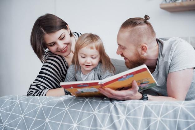 Padre, madre e figlia piccola, leggendo il libro per bambini su un divano nel soggiorno. la grande famiglia felice ha letto un libro interessante in un giorno festivo. i genitori amano i loro figli