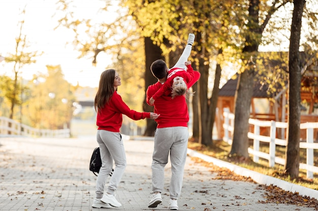 Padre, madre e figlia piccola stanno camminando nel parco d'autunno, la famiglia felice si diverte all'aria aperta.