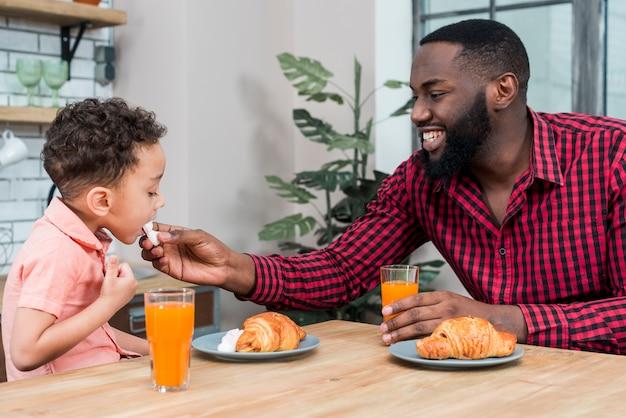 Padre nero che alimenta il figlio con i dolci