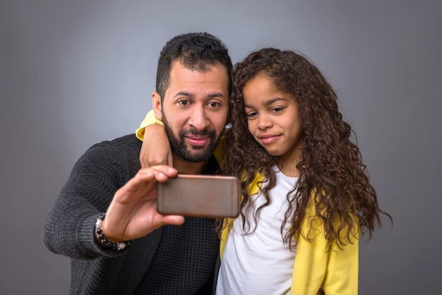 Padre nero che prende i selfie con sua figlia