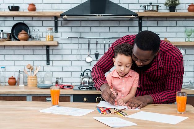 Padre nero e figlio disegno al tavolo