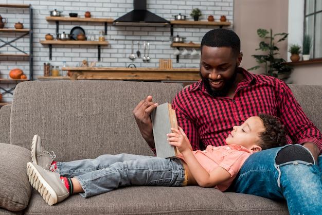 Padre nero e figlio leggendo il libro sul divano