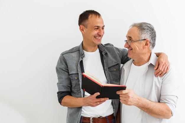 Padre senior con il figlio adulto che parla, fondo isolato.